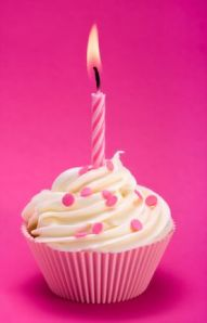 Pink birthday cupcake against a magenta background